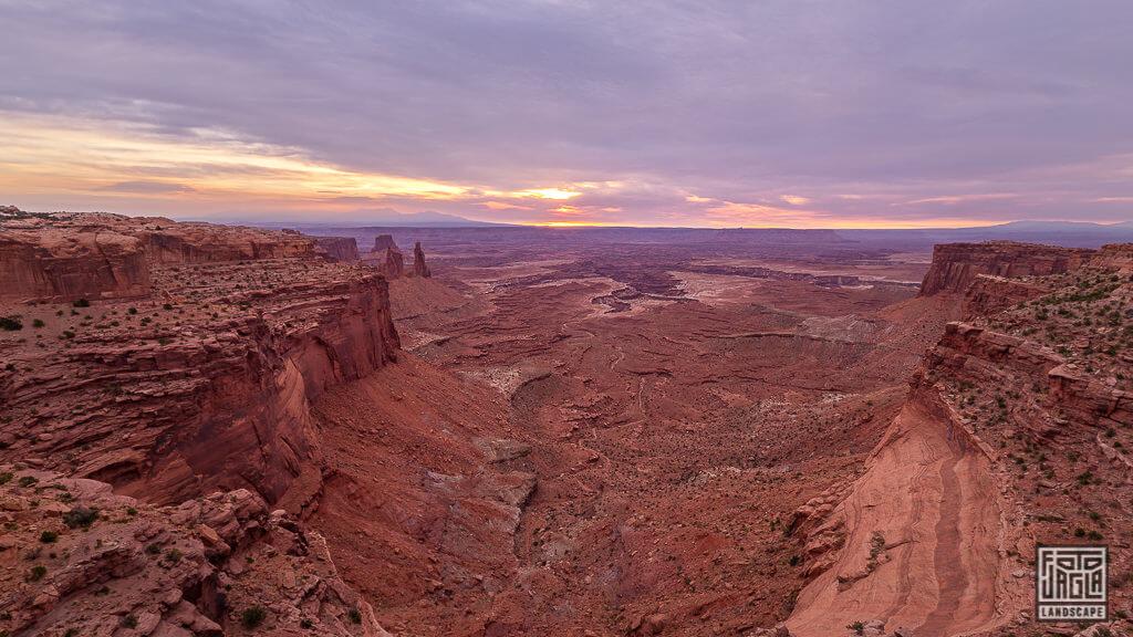 Blick vom Mesa Arch Steinbogen zum Sonnenaufgang hinunter ins Tal des Canyonlands National Parks in Utah